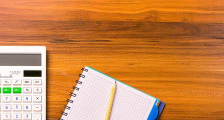 The Calculate, notebooke and pencil on wooden table.