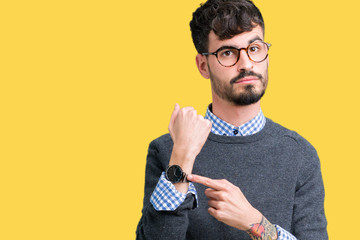 Young handsome smart man wearing glasses over isolated background In hurry pointing to watch time, impatience, upset and angry for deadline delay