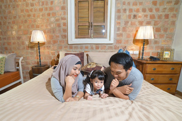 Asian Muslim family being playful on the bed at home.The parents enjoy with their adorable child with smiling and happiness. Concept is happy family day