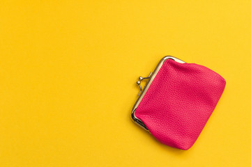Pink wallet on yellow background . Close up. Top view