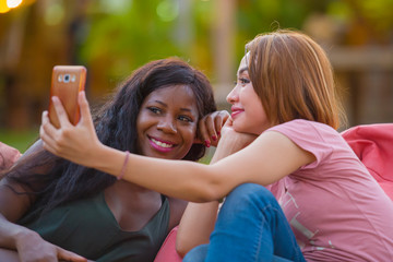 young happy and beautiful black afro American woman enjoying holidays at tropical resort with Asian girlfriend taking selfie picture with mobile phone together
