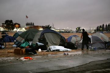 A man walks through the rain to a tent near a Walmart in Chico