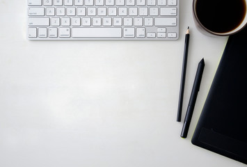 White wooden table with keyboard, graphics tablet, pen, pencil and a cup of black coffee. Workspace top view with copy space.