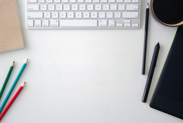 White wooden table with keyboard, graphics tablet, pen, black and color pencils, craft notebook and a cup of coffee. Workspace top view with copy space.