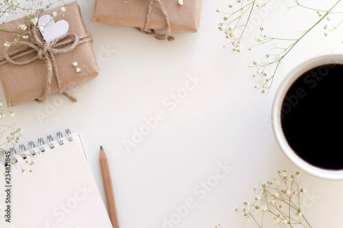 Notebook with pencil, gifts in craft paper with heart decoration, cup of black coffee, branches of little flowers on the white background. Romance, Mother's Day concept. Top view, copy space, mock up