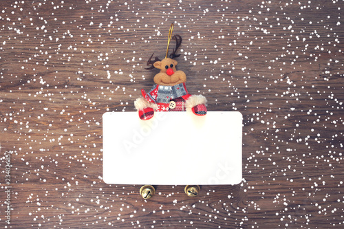 rudolph the deer holding a blank paper template with snowfall new year card christmas