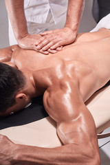 two young man, 20-29 years old, sports physiotherapy indoors in studio, photo shoot. Physiotherapist massaging muscular patient back with his hands close-up.