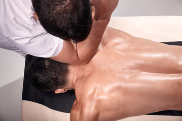 elevated view, two young man, 20-29 years old, sports physiotherapy indoors in studio, photo shoot. Strong Physiotherapist hard massaging, relaxed but muscular patient neck back side, with his elbow.