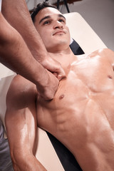 two young man, 20-29 years old, sports physiotherapy indoors in studio, photo shoot. Physiotherapist massaging muscular patient chest abdomen with his hands, upper body shot, with abdomen.