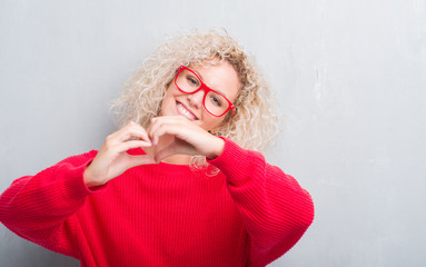 Young blonde woman with curly hair over grunge grey background smiling in love showing heart symbol and shape with hands. Romantic concept.