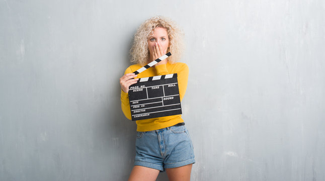 Young blonde woman over grunge grey wall holding calpboard of movie cover mouth with hand shocked with shame for mistake, expression of fear, scared in silence, secret concept