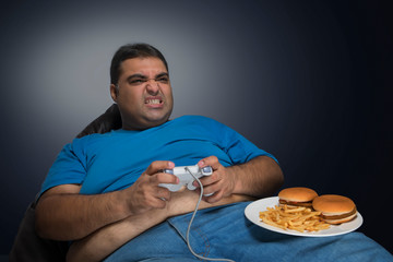 Obese man with belly visible out of his shirt seriously playing video game with a plate of burgers and french fries on his thigh