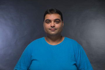 Portrait of smiling fat man against a black background