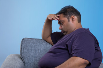 Side view of worried obese man sitting on sofa with hand on forehead