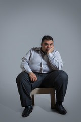 Overweight man sitting on chair in sad mood with chin resting on hand