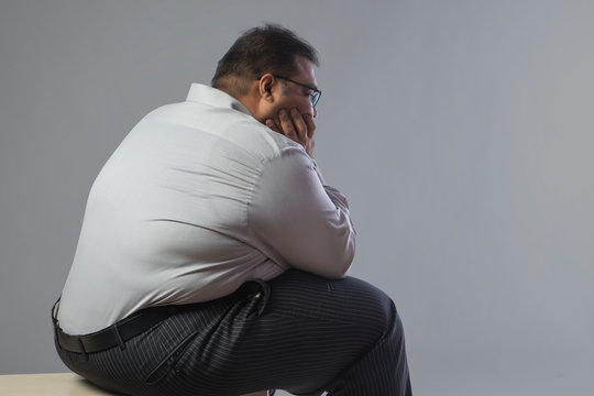 Side view of obese man sitting in sad mood with chin resting on hand