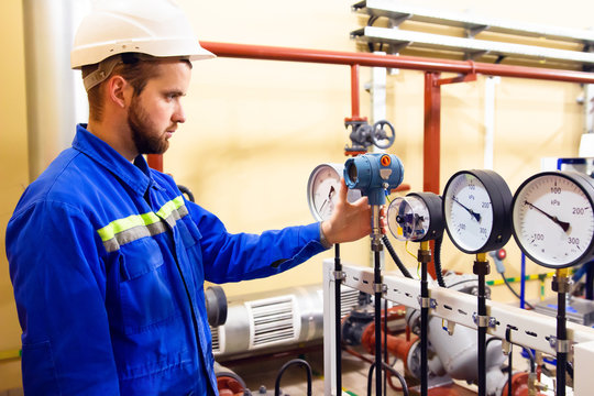 Technician worker on oil and gas refinery checks pressure manometers.