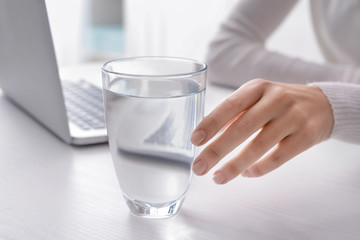 Woman taking glass of fresh water from white table