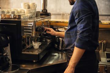 Barista preparing fresh aromatic coffee in cafe