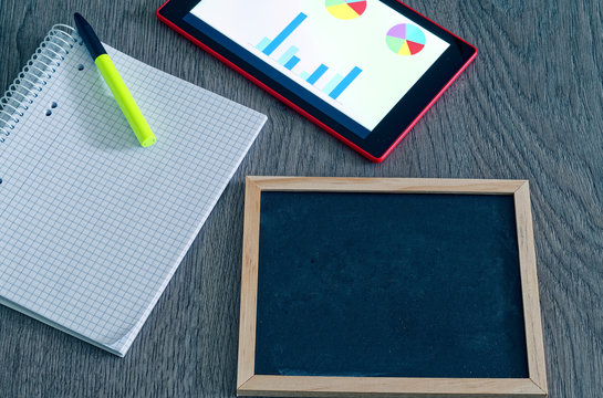 Blackboard for labeling with a block and a green pen and tablet with graphs diagrams and statistics