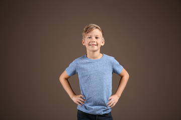 Cute boy in t-shirt on color background