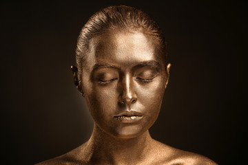 Beautiful young woman with golden paint on her body against dark background