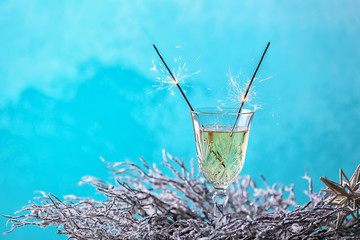 Festive Christmas sparklers in glass with champagne on color background
