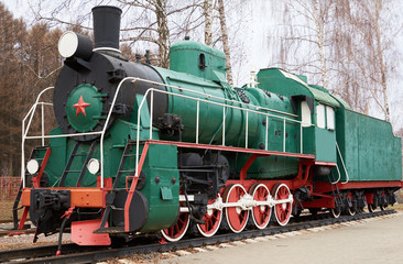 Side view of classic old green soviet steam locomotive with red star on rail tracks