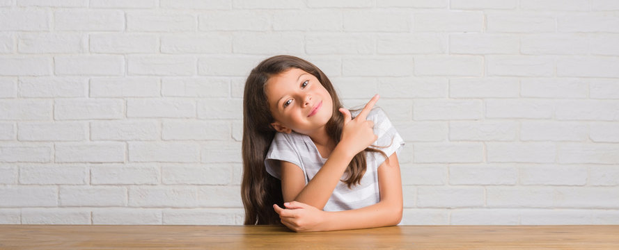 Young hispanic kid sitting on the table at home cheerful with a smile of face pointing with hand and finger up to the side with happy and natural expression on face looking at the camera.