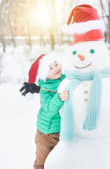 Happy boy in red christmas hat embraing snowman at sunset