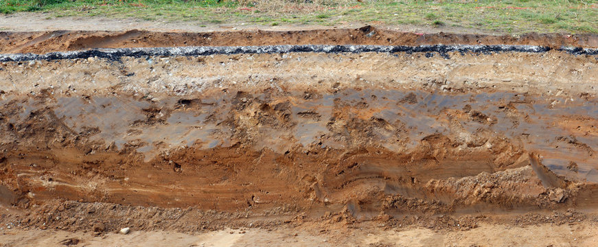 Cross-section of the pavement with layers of clay sand and asphalt. Panoramic collage from several outdoor photos