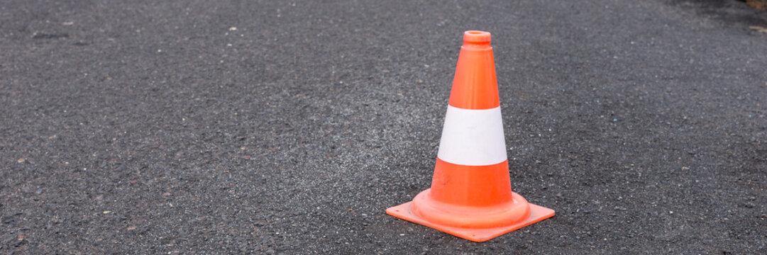 Red white road car safety cone on black asphalt