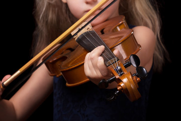 Little blonde girl playing the violin isolated on black background
