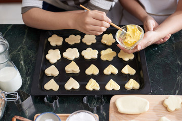 Hands of women applying soft butter on cookies before baking