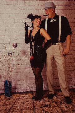 a girl with short black hair with a bandage with sequins and feathers on her head in a dress with sequins in the Chicago style of 20 years, with a man in a white shirt with suspenders and a black hat