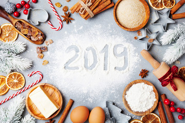 Bakery background with ingredients for cooking decorated with fir tree and new year 2019. Flour, brown sugar, eggs and spices top view.