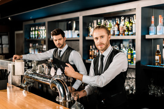 Handsome male bartenders working in bar