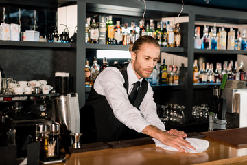 Bartender cleaning wooden bar counter with white napkin