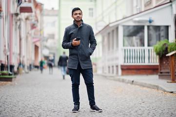Stylish indian hindu man in gray coat posed on street.