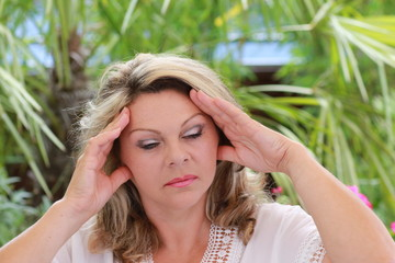Woman with severe migraine holding her head