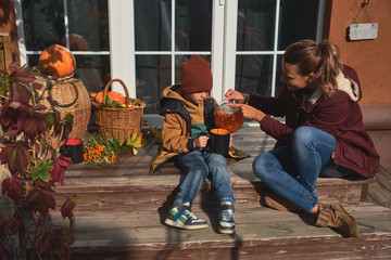 Cheerful young mother drinks sea buckthorn tea with her charming son, sitting on the porch of a pleasant rural house.