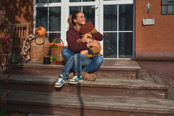 Happy young mother hugs her young son, both sitting outside on the porch.