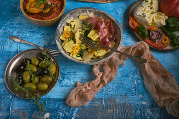 A delicious rustic salad snack with fresh vegetables, mozzarella, olives and pasta with jamon on a turquoise countertop. Healthy and environmentally friendly food. Farm products. Healthy lifestyle.