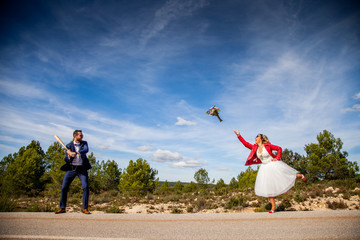 Bride throws her bouquet while groom prepares to hit him with a baseball bat