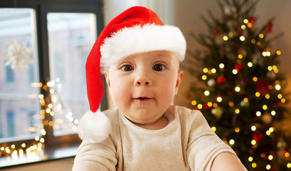 childhood, holidays and people concept - close up of little baby boy in santa hat taking selfie over christmas tree lights background
