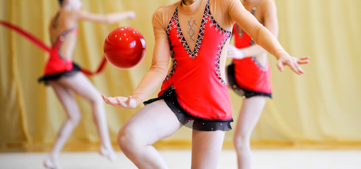 artistic gymnast dancing with red ball