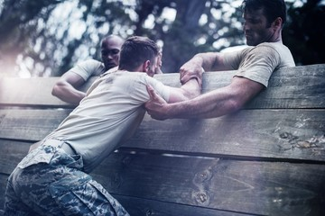 Soldiers helping man to climb wooden wall