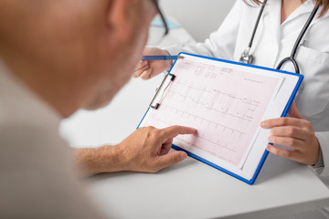 medicine, age, health care, cardiology and people concept - close up of senior man and doctor with cardiogram on clipboard at hospital