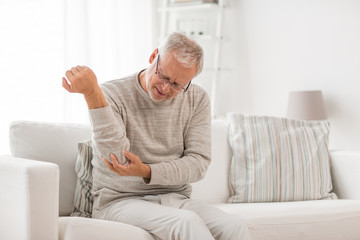 people, health care and problem concept - unhappy senior man suffering from elbow pain at home