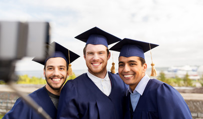 education, graduation, technology and people concept - group of happy international male students in mortar boards and bachelor gowns taking picture by smartphone selfie stick outdoors